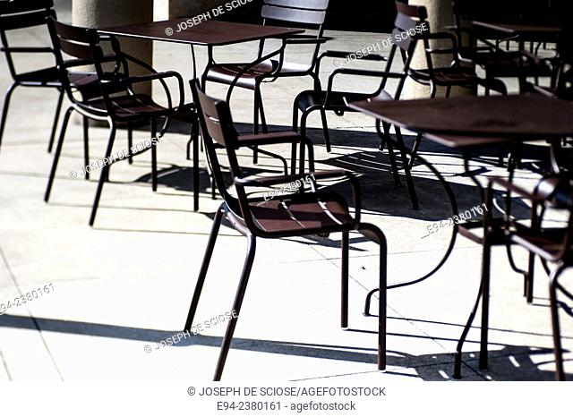 Silhouette of tables and chairs on the sidewalk of an outdoor cafe