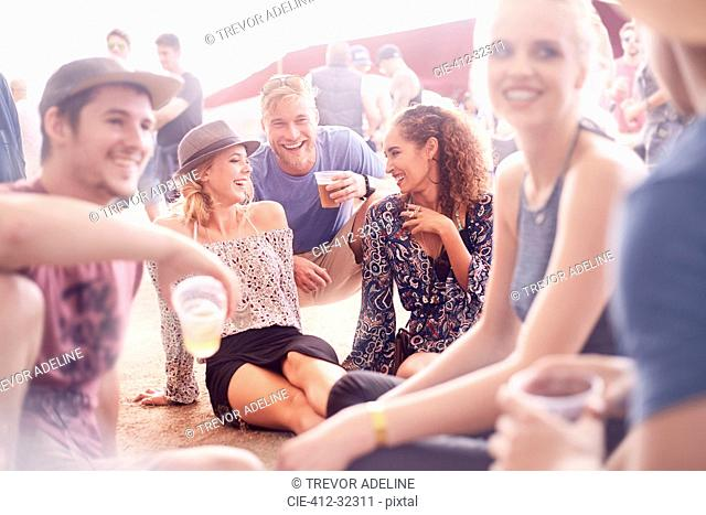 Young friends hanging out drinking beer and talking at music festival