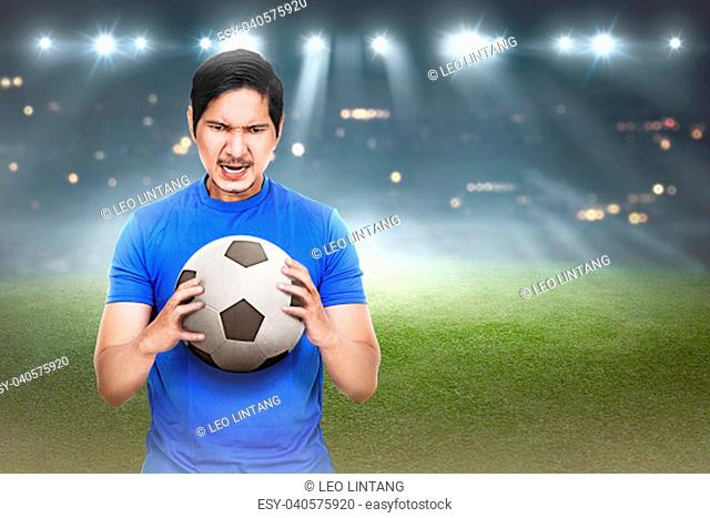 Attractive asian soocer player with ball on his hand at stadium