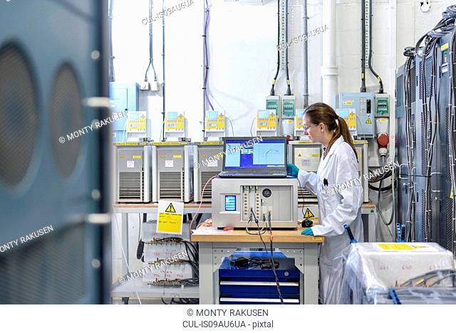 Female scientist with battery aging test equipment in battery research facility