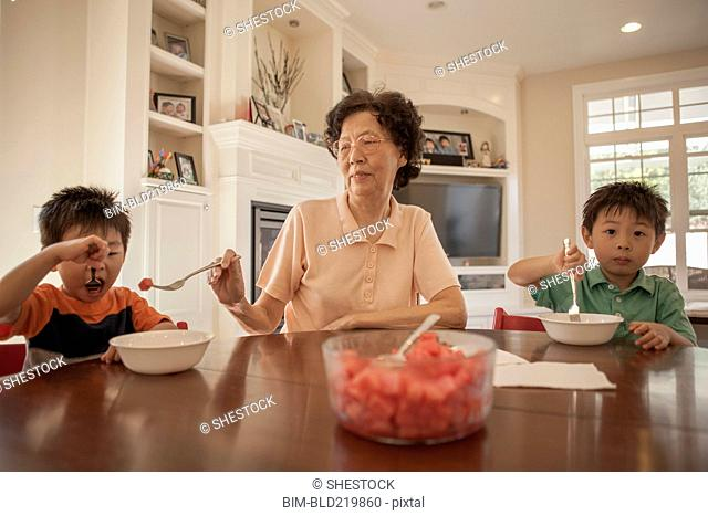 Asian grandmother feeding grandsons at table