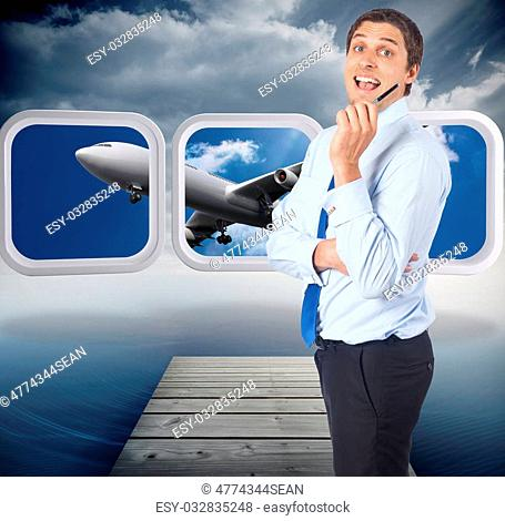 Thinking businessman holding pen against cloudy sky over ocean