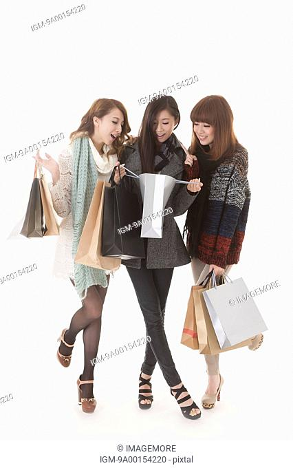 Girlfriends shopping together and looking into shopping bag