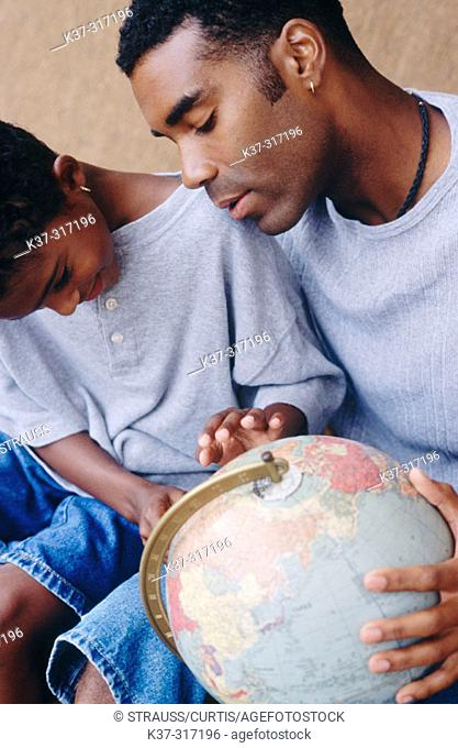 African-American father and son looking at globe