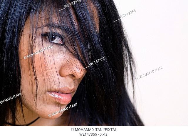 Serious young woman hair covering face