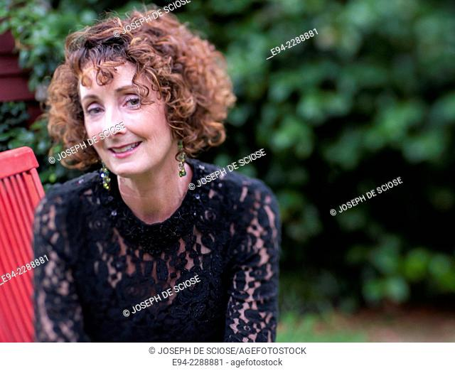 Smiling 50 year old woman with curly black hair looking at the camera