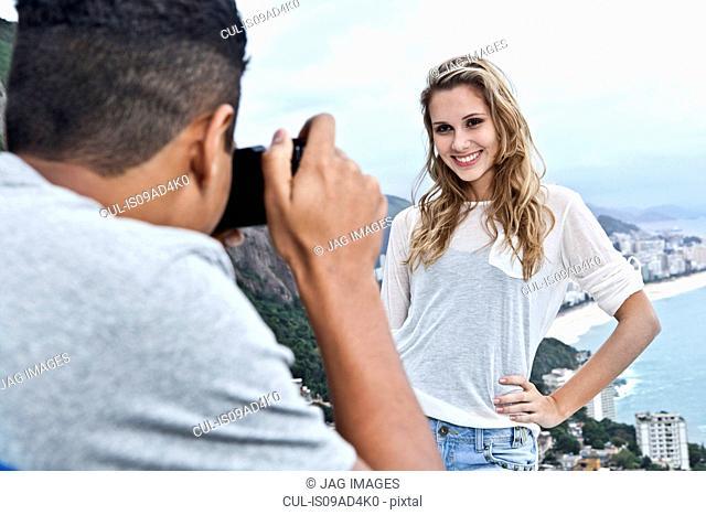 Young man photographing girlfriend, Casa Alto Vidigal, Rio De Janeiro, Brazil