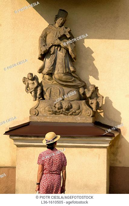 Woman looking at the statue of Saint John Nepomucene, Poland. Cieszyn