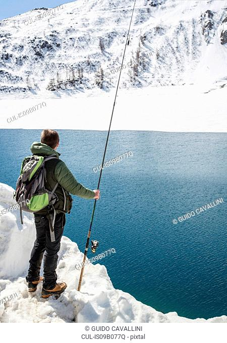 Mid adult man, fishing, Morasco lake, Morasco, Val Formazza, Piemonte, Italy