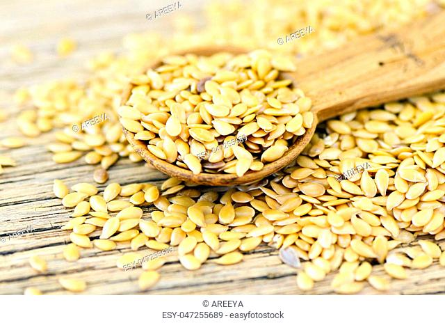Spoonful of golden flax seed on wood background