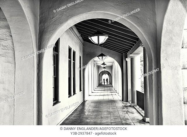 Long, outdoor hallway with arched doorways and two people at the end