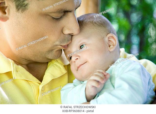 Father kissing son