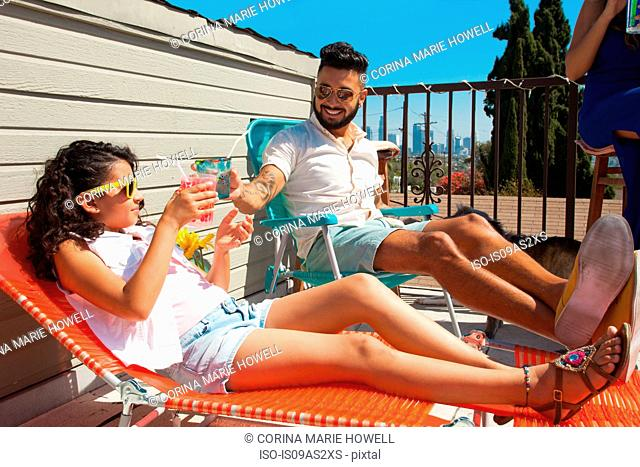 Girl and her father toasting with juice drink on patio