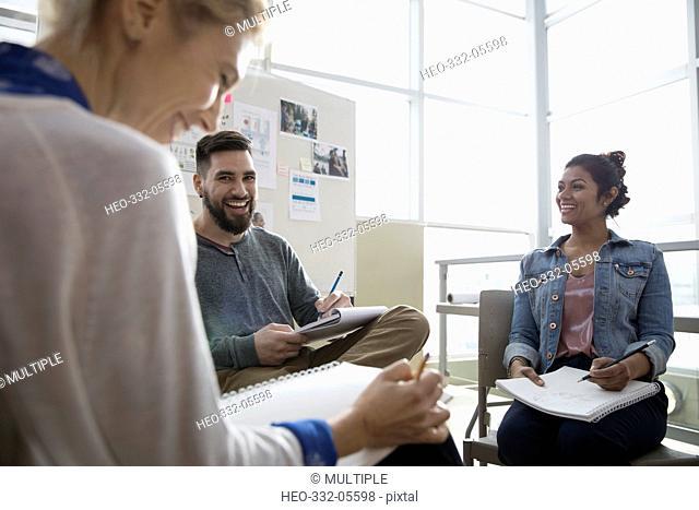 Smiling creative designers brainstorming in office meeting