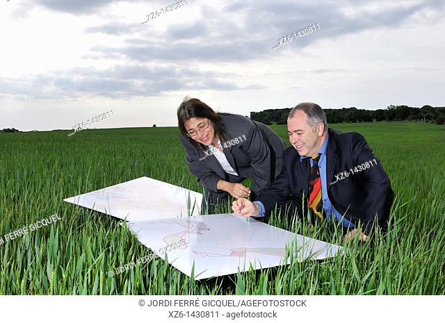 businesswoman and businessman with blueprints in the field
