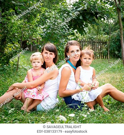 two young mums and two little girls sitting on grass looking at camera