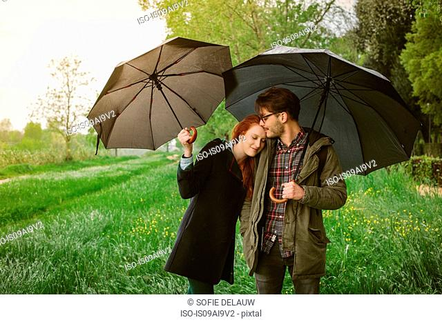 Couple walking in park under umbrellas