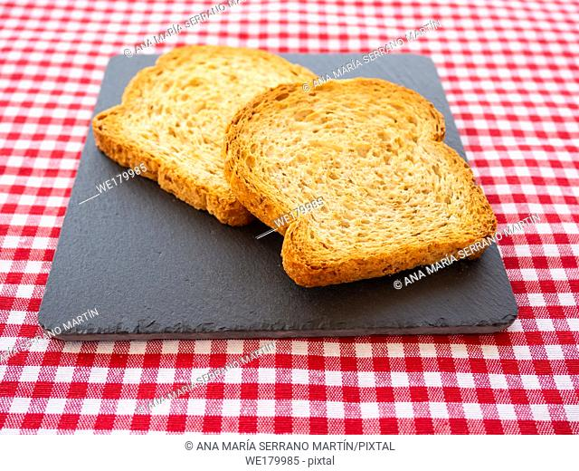 Two slices of toast on a slate plate and tablecloth vintage style