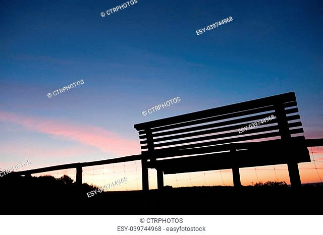 silhouette of an empty timber bench at sunset