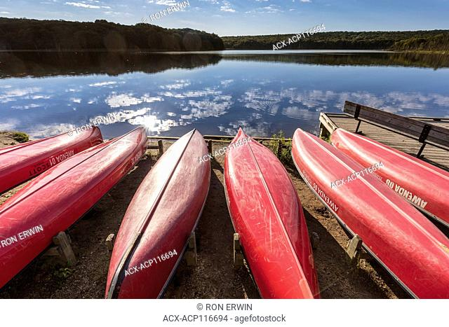 Red canoes on the shore of Kettle's Lake in Awenda Provincial Park, Ontario, Canada