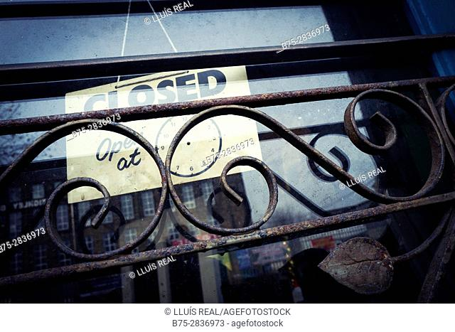 """Close-up of a shop door with an iron grate """"Closed"""" sign. Keighley, Bradford, West Yorkshire, UK"""