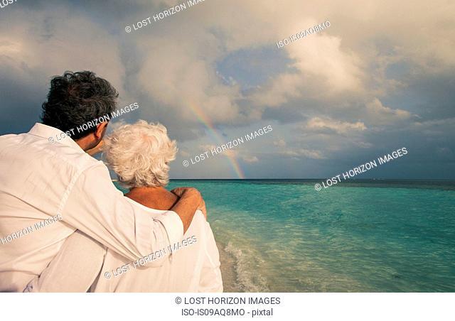 Senior couple looking at rainbow over sea, Maldives