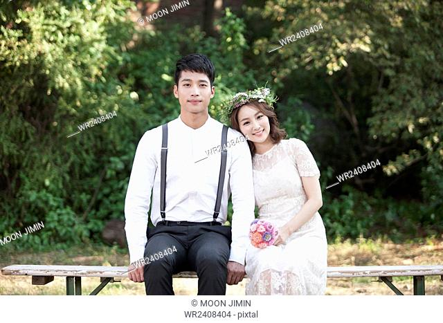 Bride and bridegroom together outside seated on a bench