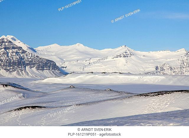 Snow covered mountains along the Jökulsárlón glacier lagoon in winter, glacial lake in southeast Iceland