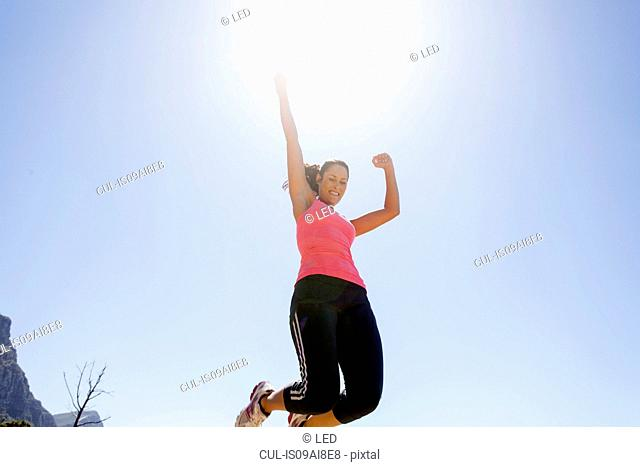 Female jogger jumping in mid air