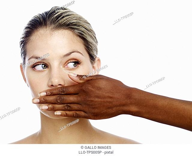 Woman's Hand in Front of Another Woman's Mouth  Studio Shot
