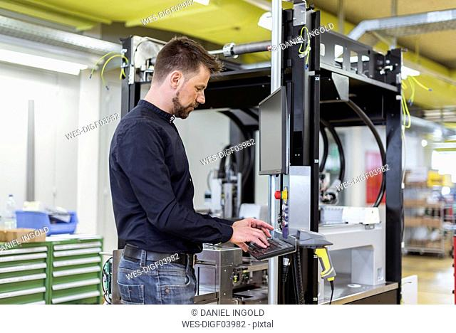 Man in factory operating machine
