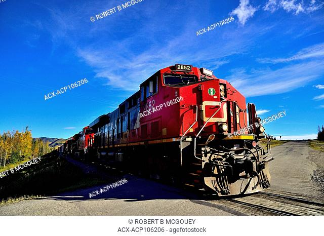 A close up image of a Canadian National freight train engine crossing the two lane road near Brule Alberta Canada