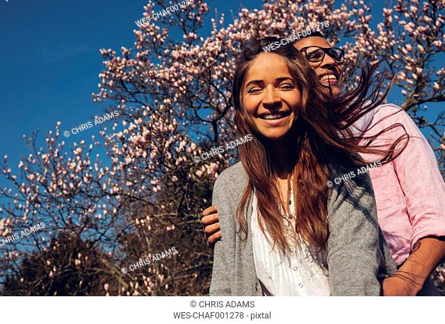 Happy young couple embracing in park