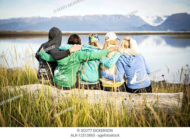 Five friends hang out on a driftwood log along coastal Homer, South-central Alaska; Homer, Alaska, United States of America