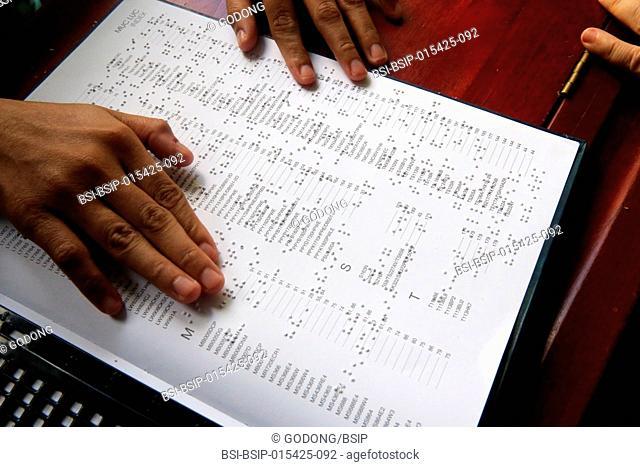 Vietnam. Center for blind children. Girl reading braille