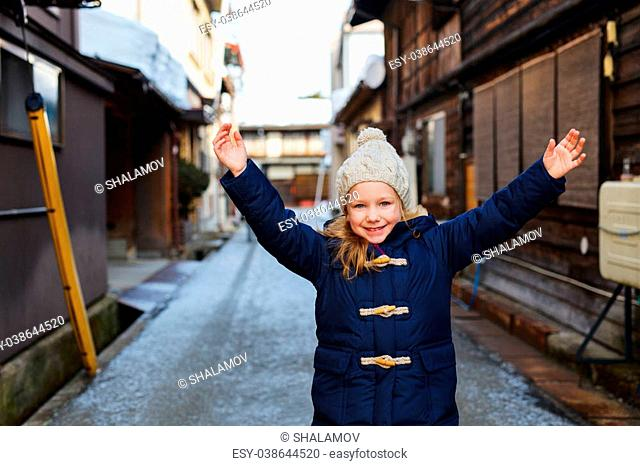 Adorable little girl outdoors on beautiful winter snow day in little town in Japan