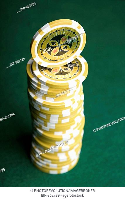 Yellow poker chips, stacked on green felt