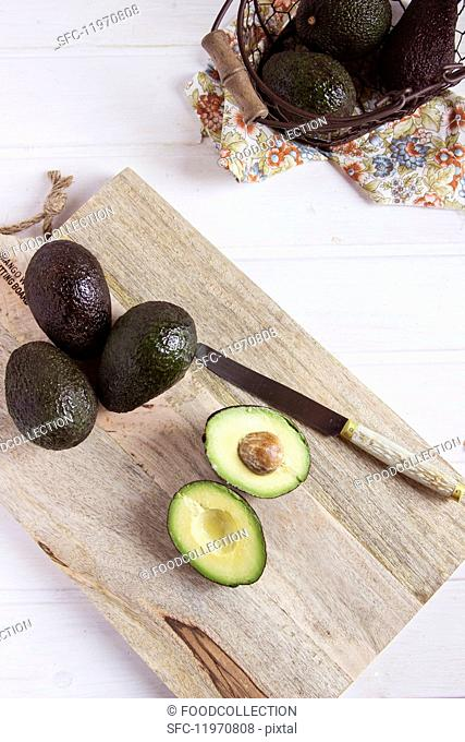 Whole avocados and a halved avocado on a wooden board (seen from above)