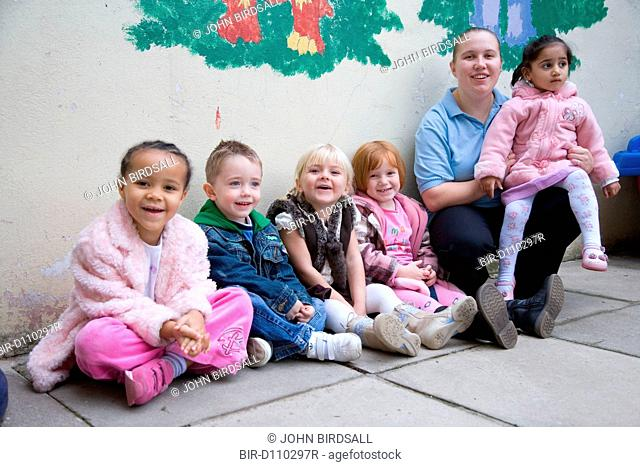 Group of playschool children with care assistant at breaktime