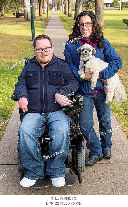 Disabled husband with his wife and their pet dog posing for a family portrait in a park in autumn; Edmonton, Alberta, Canada