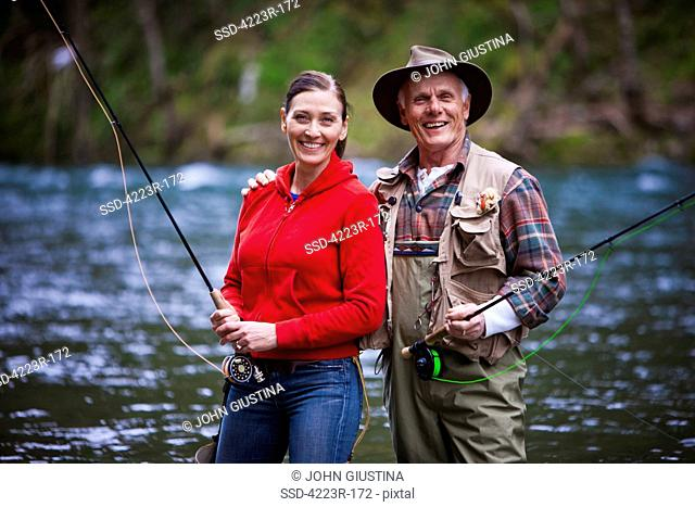USA, Washington, Vancouver, Portrait of smiling couple fishing in river