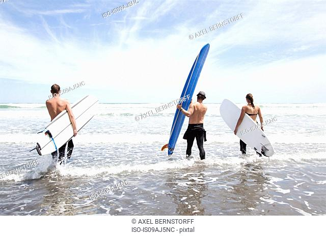 Male and female surfer friends standing in sea with surf boards