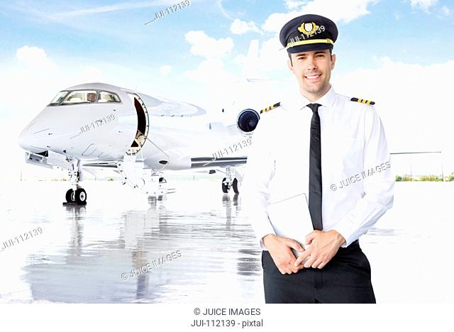 Smiling pilot standing in front of private jet