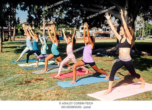 Schoolgirls practicing yoga warrior one pose on school sports field