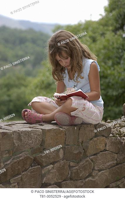 girl writing a diary in the field, Asturias, Spain