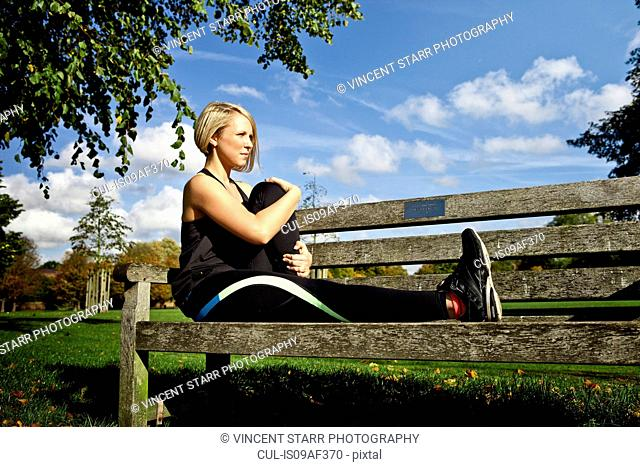 Woman bending leg on park bench