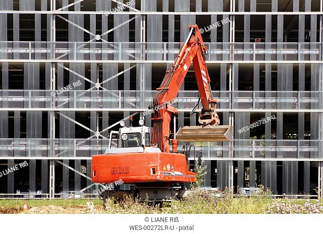 Excavator in front of house facade