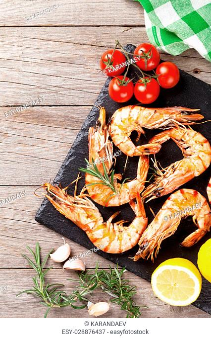 Grilled shrimps on stone plate over wooden table. Top view with copy space