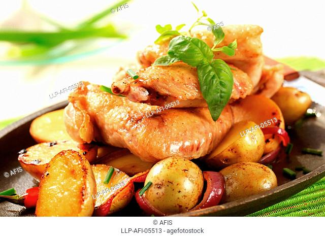 Chicken wings and potatoes sprinkled with chives