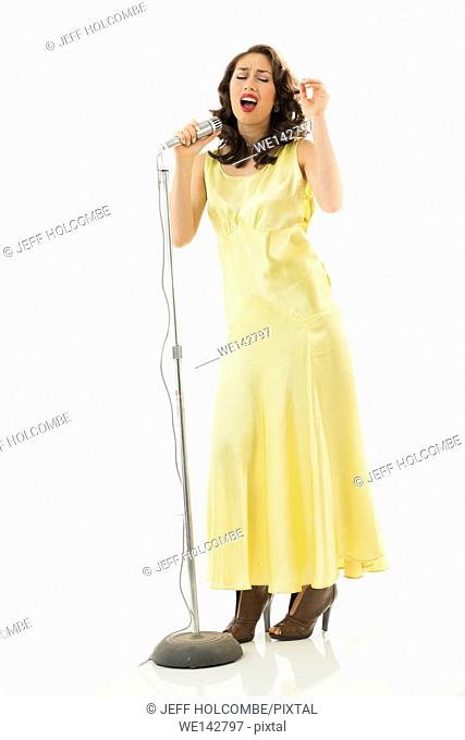 Beautiful young woman full length in vintage yellow dress, singing into microphone with great emotion and intensity, one arm raised
